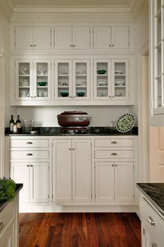 butler's pantry. white inset cabinets, dark counter, glass front traditional kitchen
