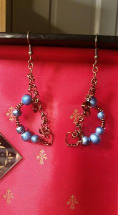 Beautiful blue, pearlized glass beads on a hand crafted wire frame, with dangling spirals and a twisted metal heart to accent this gorgeous design. These earrings are featured on hooks so they dangle freely. As with my other vintage looking pieces, these are made with nickel free materials.