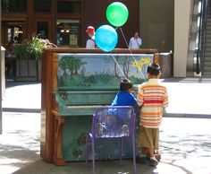 Two boys with balloons playing on a painted piano (16th Street mall in Denver, Colorado, USA)