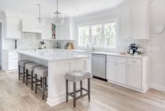 The Kitchen: Roseland Project -- White and grey kitchen, white kitchen cabinets, Cambria Torquay Quartz countertop, marble herringbone backsplash, west elm glass globe pendant lights, frigidaire double ovens, frigidaire refrigerator, danze professional faucet, vero beach interior designer, Cute & Co.