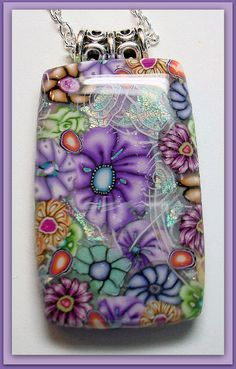 No full tutorial, but artist Sherri Kellberg says she gets this beautiful effect by mixing and layering mille fiore flower canes and using faux dichroic glass techniques. Then she sands the piece and coats with resin. Beadazzle Me Polymer Jewelry: Millifiore Meets Faux Dichroic Glass