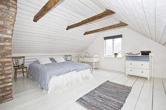 czerwona cegła,białe deski,drewniane belki pod skośnym sufitem,szara narzuta w białej aranżacji sypialni z drewnianymi belkami i czerwoną cegłą,drewniane belki na suficie w bialej sypialni,biale wnętrza sypialni z drewnianymi belkami na sufi - Lovingit.pl