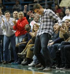 Aaron Rodgers putting on the championship belt at a Milwaukee Bucks game.