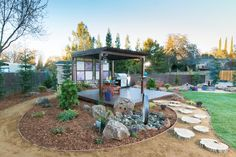 This backyard garden features a pergola and dining area flanked by an Asian-inspired garden, with a fire pit just a few steps away.