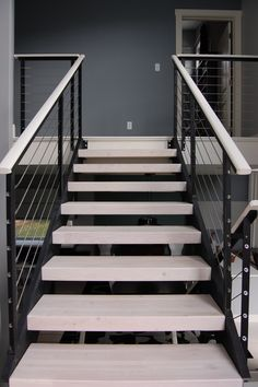 I love this modern look with the black aluminum posts and the IPE wood handrail painted white.  What do you think of this deck railing idea?