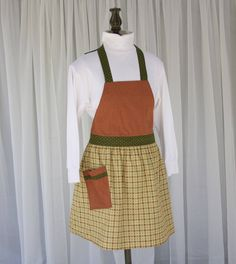 Description: Bring little Italy to your kitchen. From pizzaz to plaid, this reversible apron allows you to choose between playful and classic. One side offers a fun Italian theme and the reverse has a vintage plaid skirt with a coordinating bodice, emulating old Italy. Both feature rusty reds and olive greens. Our original pattern includes a flirty gathered skirt and contrasting pockets and ties. Product Details 100% cotton Handmade Reversible 29 long x 24 ½ wide 35 waist straps 26 ¼ neck s... Italian Theme, Vintage Apron, Little Italy, Gathered Skirt, Plaid Skirts, Olive Green, Bring It On, The Originals, Trending Outfits