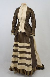 Striped silk/velvet two-piece bustle dress, 1870s. The stately silhouette is enhanced by the strong chiaroscuro effect of the striped fabric of bronze/gold corded silk and black velvet. The skirt hem, pleated ruffles, cuffs, and bustle back trim are of matching black and gold satin. The ensemble is meticulously constructed and finely finished on the inside with bound seams. The gown makes such a strong presentation that it could be the focal point of any costume display.