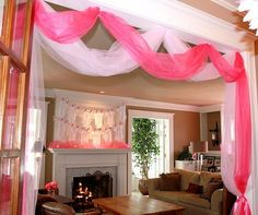 love the clothesline of onesies for decor and pink tulle swags ~ girls baby shower