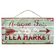 """Do you have an undying affinity for all things vintage? This gorgeous Antique Fair Flea Market Sign is right up your alley! Featuring cream-toned edges and flower accents, a pale green face with red distressing, red text and a red arrow, this completely shabby-chic MDF sign is the perfect addition to your home décor!    Dimensions:      Length: 12 3/8""""    Width: 24""""    Thickness: 3/4""""      Hanging Hardware:      2 - Sawtooth Hangers (10 1/2"""" from ..."""