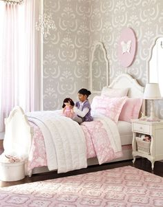 A decorative stencil on the walls, framed mirrors hung on either side of the bed and a plush medallion rug have similarly ornate silhouettes that make this room feel fit for royalty. The bedding and a plaque above the headboard add liveliness to the theme with butterflies. Gray, lavender and cream create a sophisticated palette, and a glittering chandelier brings warmth.