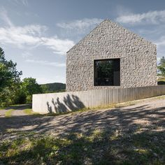This take on a traditional Slovenian cottage by Dekleva Gregorič Arhitekti features cast concrete walls inlaid with stone to create a rugged texture