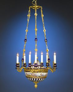 This phenomenal 9-light porcelain chandelier is beautifully crafted in the style of the famed Sèvres Porcelain Maufactory. A gorgeous example of Napoleon III-era artistry, this chandelier exhibits several hallmarks made famous by that illustrious firm. The brilliant cobalt blue ground sets the stage for a wealth of exceptional features, including a cast bronze ormolu gallery and candle arms, an extraordinary Bacchanalian scene hand-painted in a continuous band in the pastoral style of Rococo…