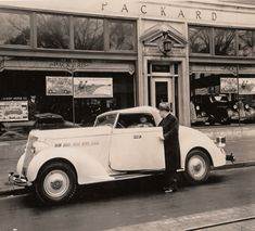 """Packard Co. file photograph of a 1936 Packard left side view, top raised, parked on street in front of Packard dealership, male handing keys to male driver. Inscribed on photo back: Packard one twenty, fourteenth series, model 120-B, 8-cylinder, 120-horsepower, 120-inch wheelbase, 2/4-person convertible coupe (body type #999), note """"Kroger"""" insignia on door panel, setting: in front of J.B. Ruby Motor Co., Charleston, W.Va."""