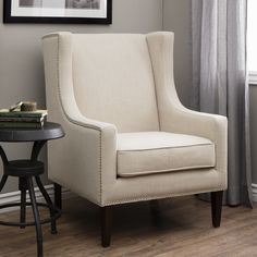 Add a modern touch to your home decor with this stylish cream chair. A lovely cream upholstery and espresso finish highlight this classic chair. This linen wing chair ties together any room and provides the perfect place to relax with a cup of tea.