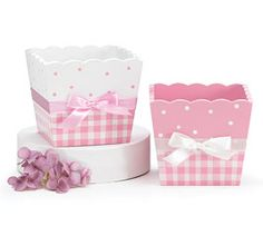 Pink and white square planter with polka dots and check pattern. Satin ribbon tied in bow around middle.  Wood