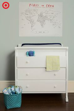 While you're waiting for Baby to arrive, set up the perfect spot for diaper changes. A multifunctional changer dresser, like the DaVinci Porter style shown, offers a changing pad on top and plenty of storage below. Add a basket as a colorful room brightener that doubles as a place to stash towels, blankets and a toy or two to engage your little one. And, above the dresser, hang a handmade wall accent, like the DIY map shown here.