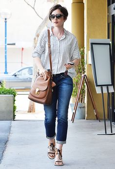 Lily Collins wore a pinstriped button-up with blue cuffed boyfriend jeans, brown crossbody bag, and tie sandals.