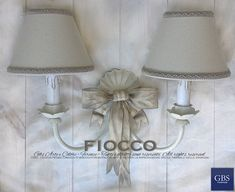 L'autentico Applique Fiocco di GBS, qui nella versione a 2 luci, con paralumi. Applique in ferro battuto decorato a mano, finitura in tempera anticata, colore bianco avorio e biscotto. Made in Florence.