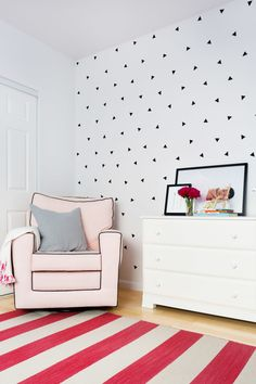 "In little Abri's room, fun geometric patterns are the norm from the striped <a href=""http://www.wayfair.com/Jaipur-Rugs-Pura-Vida-Pink-Ivory-Stripe-Area-Rug-PV51-RUG1-JCJ1894.html"" target=""_blank"">rug</a> to the triangles on the wall. They may look like a custom wallpaper, but those little shapes were hand-placed decals bought from Etsy."
