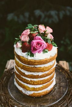 naked cake topped with fresh roses and strawberries