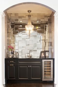 arched living room alcove is filled with black cabinets fitted with a glass front wine cooler topped with black marble framing a wet bar sink and gooseneck faucet alongside a mosaic tiled mirrored mirrored backsplash illuminated by a fringe chandelier. Beadboard Backsplash, Kitchen Backsplash, Backsplash Ideas, Mirrored Tile Backsplash, Herringbone Backsplash, Tile Mirror, Travertine Backsplash, Mirrored Subway Tiles, Antique Mirror Tiles