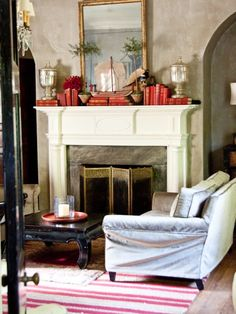 The mantel. layered with red books, mercury-glass vessels and rosemary topiary trees. A slipcovered sofa mixed with a red-and-white striped rug add a touch of comfort to the formality