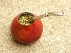 """Yerba mate (Ilex paraguariensis) y bombilla dentro de un calabacín (también llamado """"poro"""") teñido de rojo"""