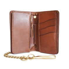 The Singleton Wallet is a mid-length wallet with three card slots, a full-sized bill slot, and one hidden pocket behind the card slots, and a large zipper pocket.  The wallet is equipped with a solid brass ring for the use of a wallet chain or leather rein.-SR