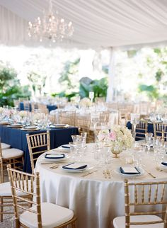 Polished navy, gold, and blush reception with cream settings with navy napkins, gold touches, and blush flowers in the centerpiece
