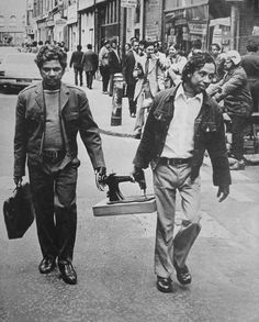 M is for Machinist. This photograph, taken in the 1970's, shows two Bengali machinists carrying a Singer sewing machine along Brick Lane. Bengali machinists became a major part of the garment manufacturing industry with the decline of the Jewish tailors in the area in the mid-20th Century. (Oral history ref: SWADHINATA TRUST)