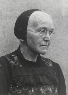Weduwe Van der Scheer uit Veessen in Gelderse streekdracht. Mevrouw Van der Scheer is gekleed in daagse dracht. Ze laat zien hoe ze de 'knipmuts' opzet. Eerst wordt het haar gladgestreken en met een bandje vastgezet, daarna wordt de zwarte ondermuts opgezet. 1945 #Gelderland #Veluwe #nieuwedracht