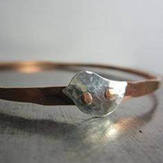 handmade silver and copper bangle with tiny bird