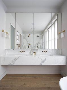 bancada de mármore e detalhes dourados em banheiro