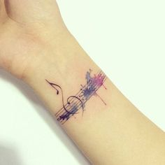 Watercolor music staff tattoo on the inner wrist.