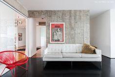 """""""Cozinha de estar"""" tem sofá branco, poltrona acapulco e piso de resina preto."""