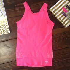 Nike Fit Dry top  racer back in bright pink This adorable top is just slightly too small for me around the shoulders.  It has been worn and you can see some slight snagging on the inside (not the exterior) from where it caught on my necklace.  Other than that in great used condition. Nike Tops Tank Tops