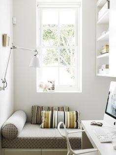 格子入りの可愛らしい白い窓と壁付けのアームランプのあるワークスペースの窓際のリーディングヌック