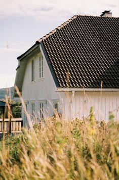Dette landlige huset er kledd med tidsriktig lektekledning og klassiske lister rundt vinduene. 😍 Husets symmetri i fasade og bygningskropp, halvt valmet og bratt tak og smårutete vinduer, gir en følelse av en helhetlig klassisk stil. Shed, Outdoor Structures, Cabin, House Styles, Home, Decor, Decoration, Cabins, Ad Home