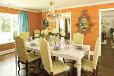 Try a nontraditional color scheme. This formal dining room jazzes up a traditional foundation with unexpected color combinations. The graphic green upholstered chairs play off of the distinctive orange-and-gold wallpaper. Gilded accents pick up the metallics in the pattern of the paper.  See this Colorful Home