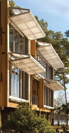 Façade consists of translucent polycarbonate hangar doors that fold horizontally. Loblolly House,  Kieran Timberlake Associates