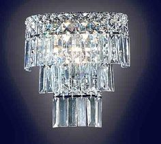 285. Crystal Sconce - Wall sconces are a brilliant way to brighten up your house. This one features rows of beautifully cut rectangular crystals that sparkle in the light, adding instant glamor to any room. This wall sconce exudes the sophistication and elegance of royalty.   10 IN W 5 IN D 10 IN H 7#