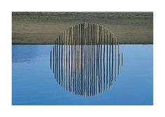 Water Cycle 3 - This sculpture was made by forming a semi-circle with sticks pushed into the sand in a beach lagoon on the West Coast of Auckland, New Zealand. When the wind dropped and the water was still the reflection made it appear as a full circle -