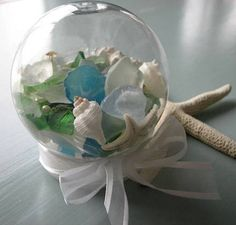 Beach decor beach globe kit includes shells, sea glass, pearls, a sand dollar, and a white starfish.