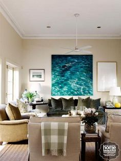 Walls painted in Dulux Ecru form a classical backdrop to a large oil painting by Martine Emdur from the Tim Olsen Gallery. Armchairs upholstered in fabrics from Warwick Fabrics and a deep moss-green velvet sofa, on top of a seagrass rug from International Floorcoverings, create a cosy sitting area.