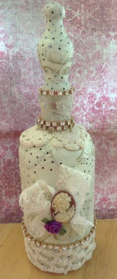 Mod Podge Bottle .. the entire bottle is Mod Podged ..  2 differnt styles of tissue paper are layered along with vintage lace, rhinestones and a b'sue cameo to make this bottle .. Designed by .. Jann Tague .. Clever Designs ..          https://www.facebook.com/#!/JewelsByJann