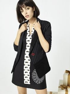 Black sleeveless blouse with an asymmetric hem, button fastening and a white contrasting print.