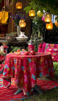 Table Art. Vibrant colors are offset with muted hanging lanterns for an inviting outdoor dining area. See more at http://pinterest.com/wineinajug/outdoor-party-lighting/