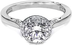 Tacori Solitaire Engagement Ring with Pave Diamond Halo: A halo of diamonds surrounds this pretty solitaire engagement ring, and its contemporary, high-polished band is accented with diamond details, adding interest from every angle.
