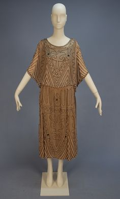 DECO BEADED DRESS, 1922. Taupe silk with tabard top over short kimono sleeve, low waist with gathered skirt and self sash, decorated in an abstract pattern of large milky white beads and smaller charcoal iridill beads, silk charmeuse attached underdress.