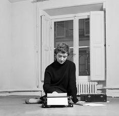 """1956. Avec """"Bonjour Tristesse"""", Françoise Sagan, une jeune fille de 18 ans, a séduit et scandalisé la France : elle a aussi emporté le plus gros succès de librairie de l'après-guerre. Avec son deuxième roman elle prouve qu'elle est un écrivain. Nous la voyons ici travailler dans son hôtel particulier ou elle vient d'aménager rue de Grenelle à Paris. Les pièces sont encore vides et les toiles sont posées par terre. Photo : Philippe le Tellier / Paris  Match"""